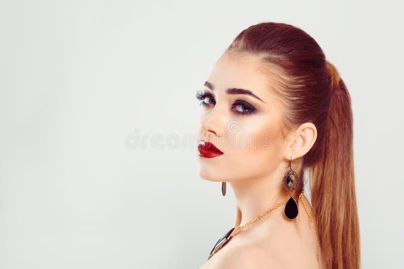 O cabelo modelo na mulher do rabo de cavalo está inclinando-se contra um fundo cinzento branco fotos de stock