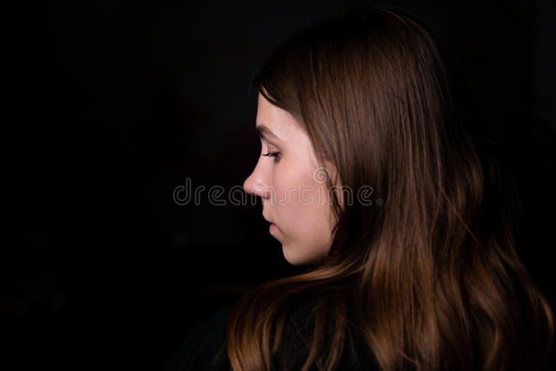 O cabelo moreno preto escuro do lado do perfil da recepção da noite da menina do retrato da roupa do fundo preto do estúdio olha  fotografia de stock royalty free