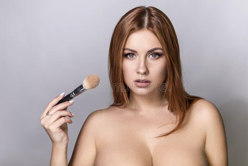 O cabelo vermelho bonito mais a aplicação do modelo do tamanho compõe com uma escova fotos de stock royalty free