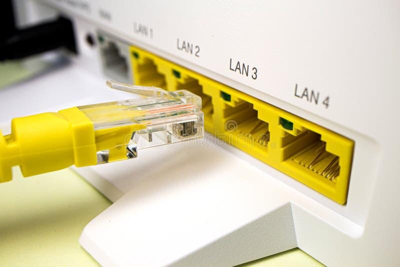 O cabo amarelo com o conector rj45 é introduzido no router da casa para o Internet imagens de stock