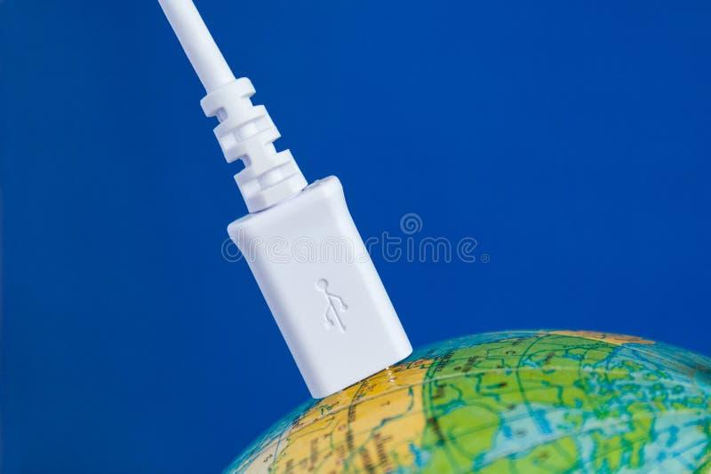 O cabo de USB é conectado ao globo Conceito fotos de stock royalty free