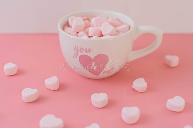O cacau quente em uma caneca do coração com coração cor-de-rosa deu forma a marshmallows fotos de stock