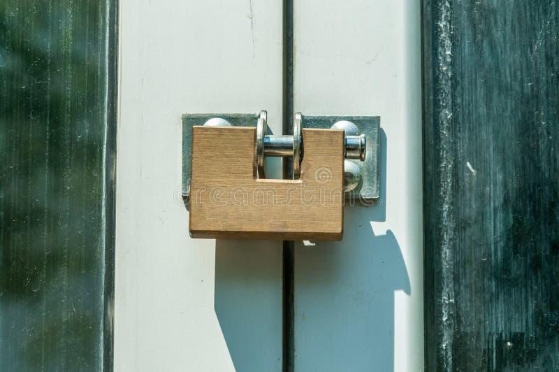 O cadeado de aço moderno dourado fechado da segurança ou da segurança nas portas de entrada fecha-se acima imagem de stock royalty free