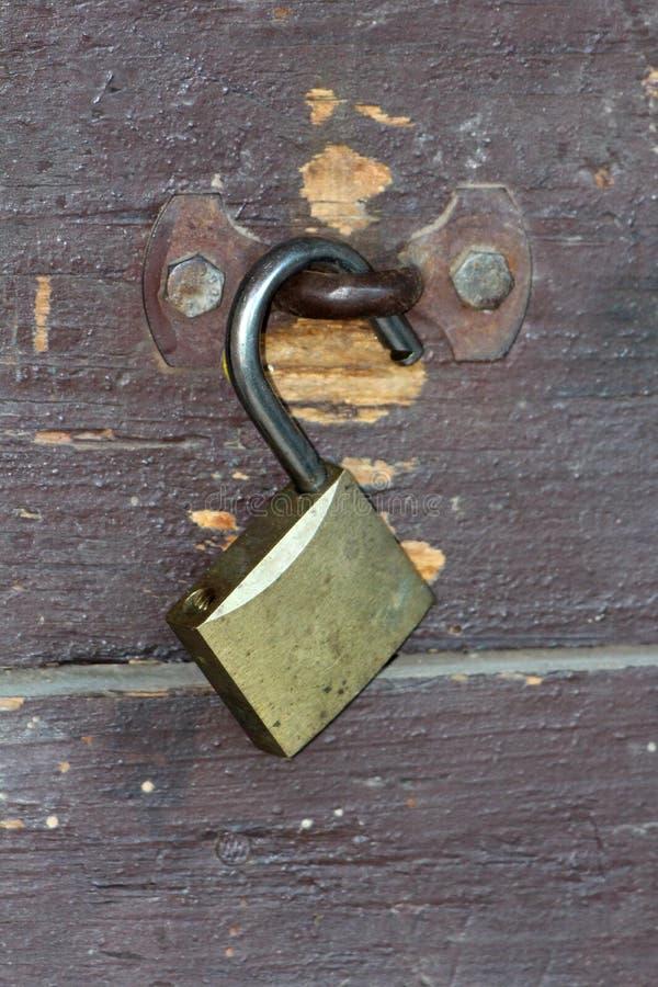O cadeado destravado saiu aberto na dobradiça oxidada do metal montada com os dois parafusos fortes em placas de madeira dilapida foto de stock