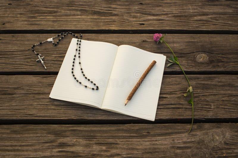 O caderno aberto da placa, o lápis de madeira e o chaplet do católico para rezam no fundo de madeira fotos de stock