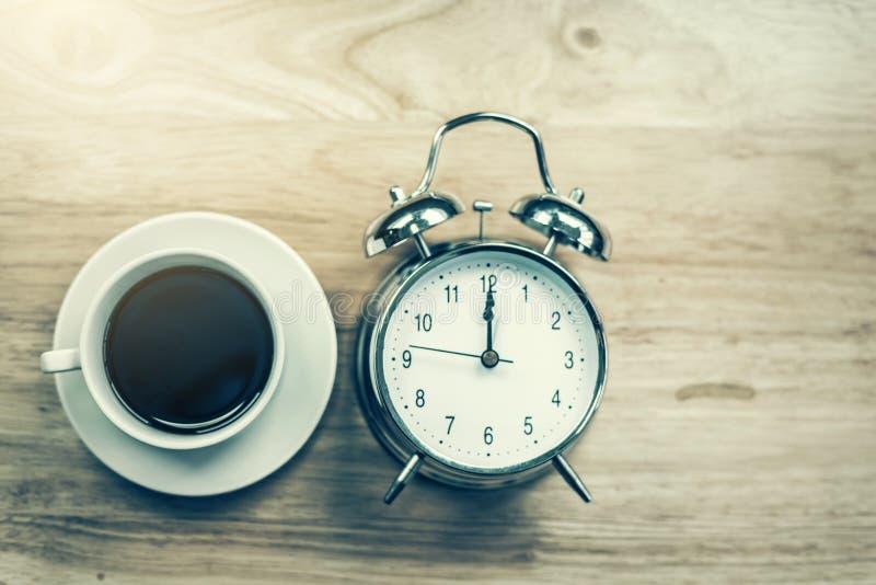 O caderno aberto do café preto com despertador antiquado corteja sobre imagem de stock