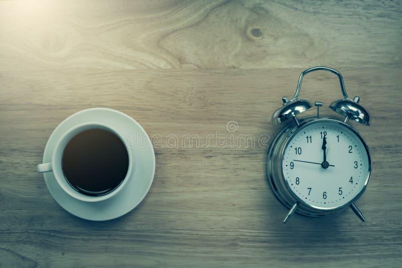 O caderno aberto do café preto com despertador antiquado corteja sobre imagens de stock