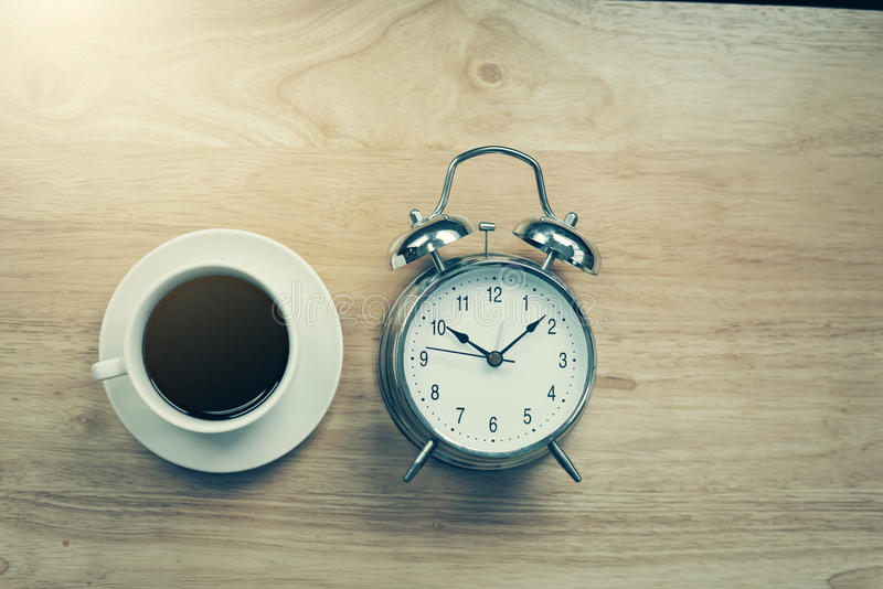 O caderno aberto do café preto com despertador antiquado corteja sobre fotos de stock royalty free