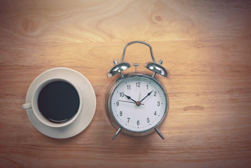 O caderno aberto do café preto com despertador antiquado corteja sobre imagens de stock royalty free