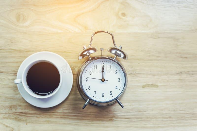 O caderno aberto do café preto com despertador antiquado corteja sobre foto de stock