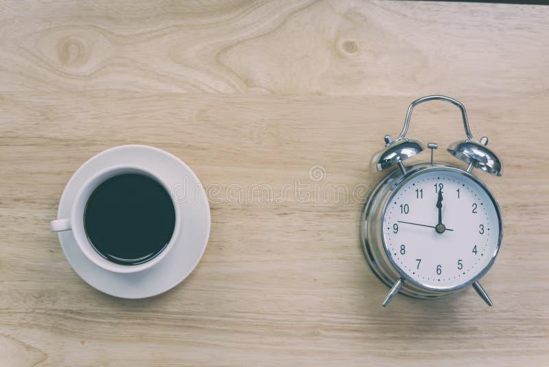 O caderno aberto do café preto com despertador antiquado corteja sobre foto de stock royalty free