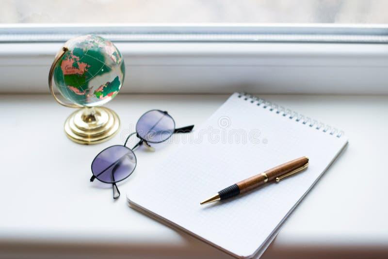 O caderno abriu na mesa branca com pena, globo e vidros pretos Vista de acima imagens de stock royalty free
