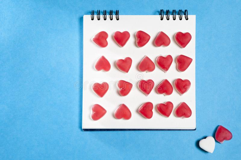 O caderno branco nas molas com um coração do marmelade em um fundo azul imagens de stock