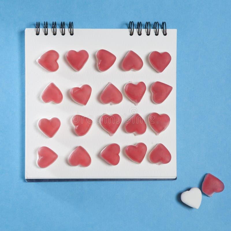 O caderno branco nas molas com um coração do marmelade em um fundo azul foto de stock royalty free