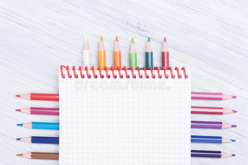 O caderno com lápis coloridos encontra-se belamente em um fundo claro imagem de stock