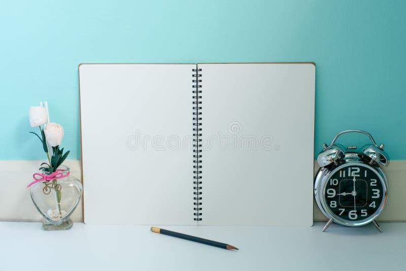 O caderno da página vazia com flores e o metal brilhante cronometram com um pe imagem de stock royalty free