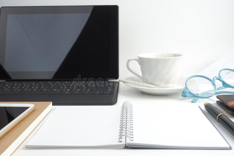 O caderno da página vazia no desktop branco com pena, café, portátil foto de stock royalty free