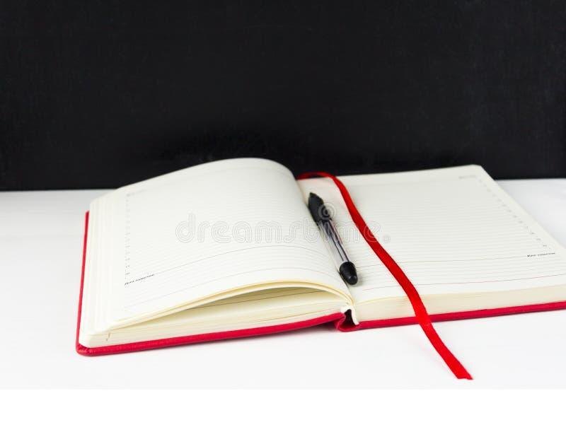 O caderno e uma pena estão na tabela imagem de stock royalty free