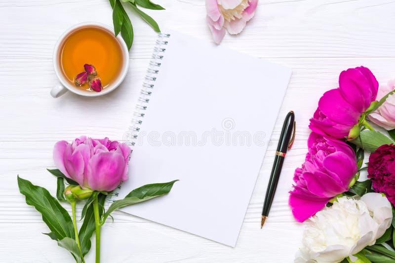 O caderno vazio com lugar para o texto, a pena, um copo do chá e peônias floresce foto de stock