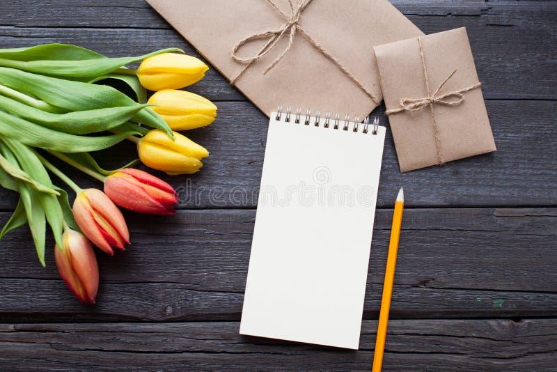 O caderno vazio, o lápis e as tulipas amarelas e vermelhas florescem no fundo de madeira do vintage Foco seletivo Lugar para o te imagem de stock royalty free
