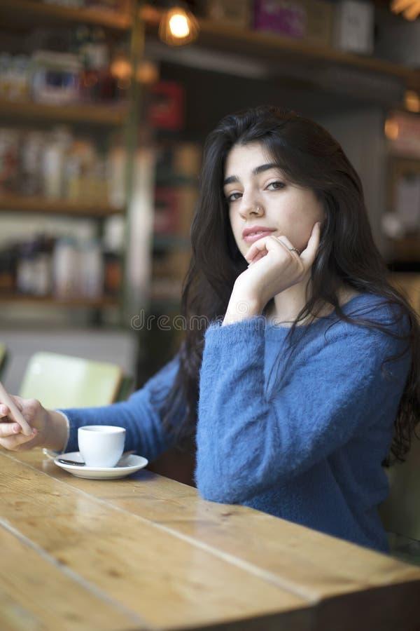 O café bebendo da jovem mulher e usa seu assento do smartphone interno no café urbano Estilo de vida da cidade do café Retrato oc fotos de stock royalty free