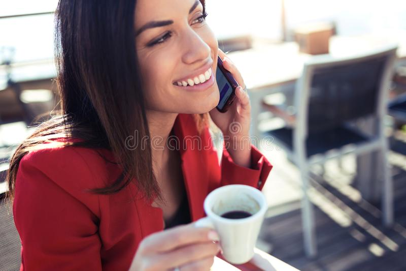 O café bebendo de sorriso da jovem mulher ao texting com seu telefone celular wodden sobre a tabela no terraço de uma cafetaria foto de stock