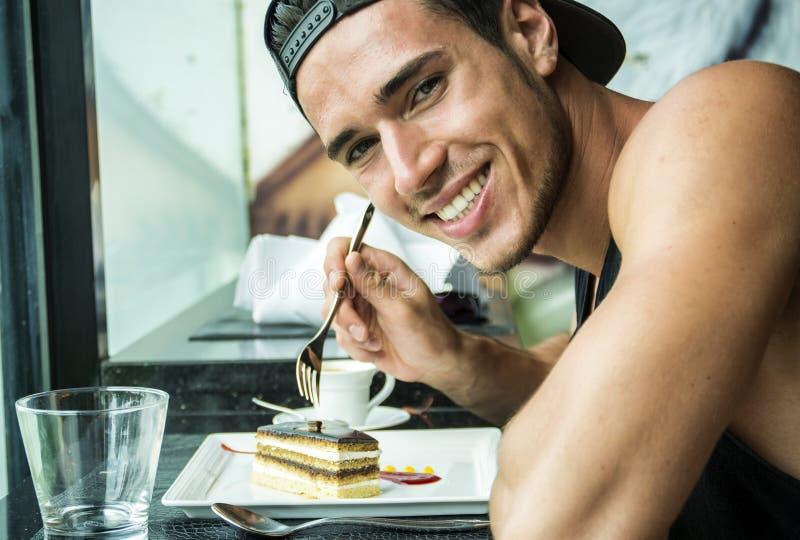 O café da manhã atrativo de homem de jovens, comendo o bolo no jantar imagens de stock