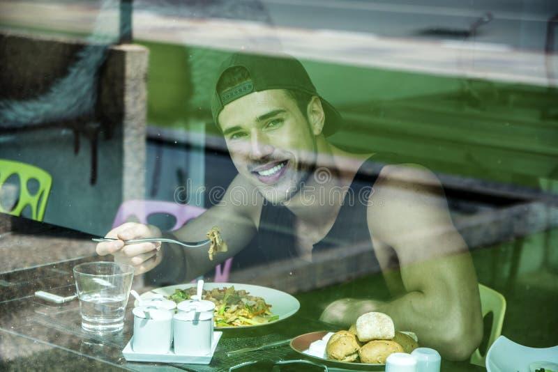 O café da manhã atrativo de homem de jovens, comendo a salada no jantar foto de stock royalty free