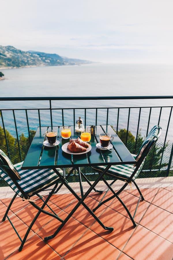 O café da manhã delicioso com café, pastelaria, e suco de laranja serviu no balcão com opinião do mar fotografia de stock royalty free