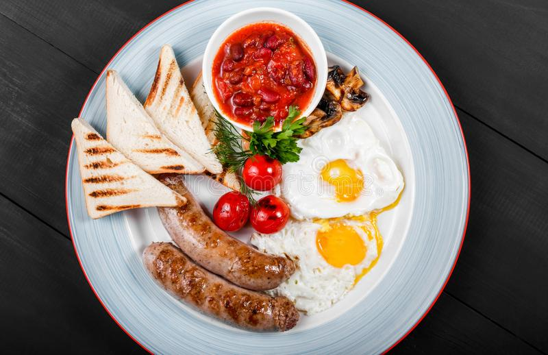 O café da manhã inglês - ovos fritos, feijões, salsicha, grelhou tomates, cogumelos, o pão brindado e o molho na placa no fundo e imagem de stock