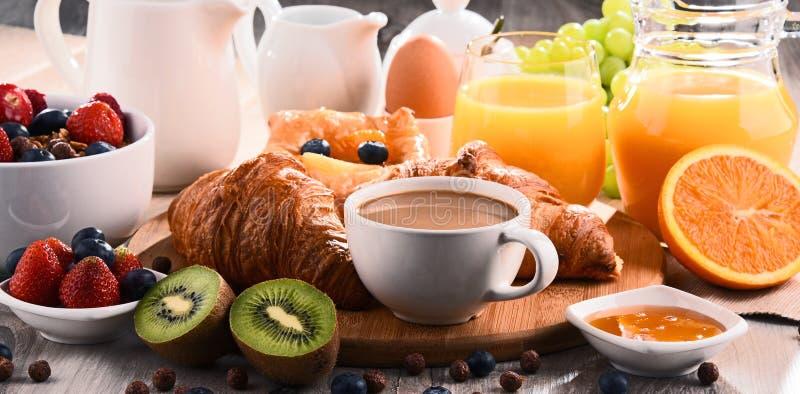 O café da manhã serviu com café, suco, croissant e frutos foto de stock royalty free