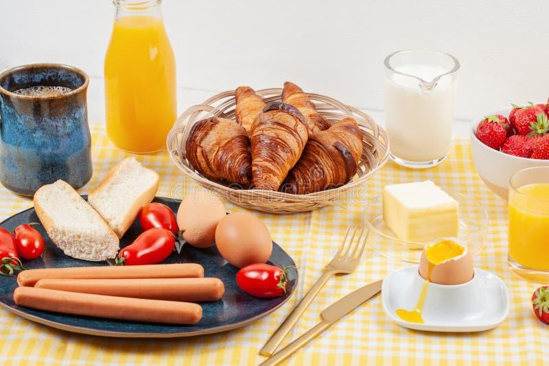 O café da manhã serviu com café, croissant, salsichas, ovos, frescos imagens de stock