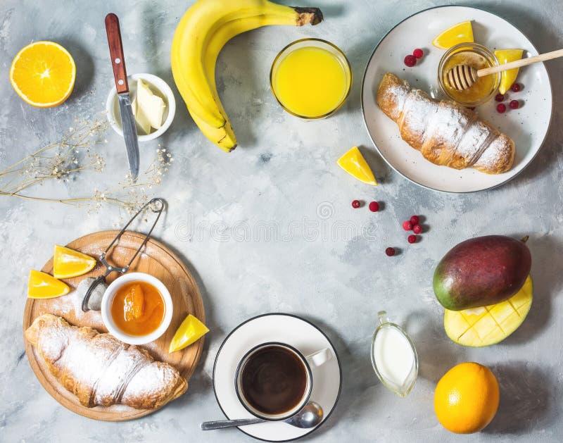 O café da manhã serviu com café, suco de laranja, croissant e frutos no fundo concreto imagem de stock