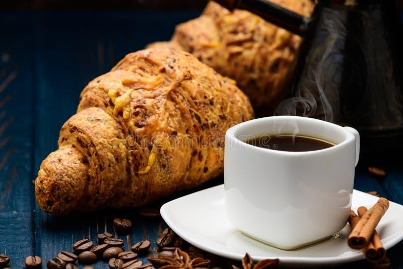 O café derrama em um copo em uma tabela de madeira azul com feijões de café e um croissant imagens de stock royalty free