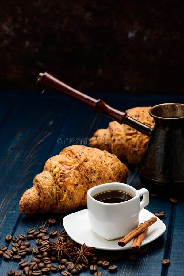 O café derrama em um copo em uma tabela de madeira azul com feijões de café e um croissant imagem de stock royalty free
