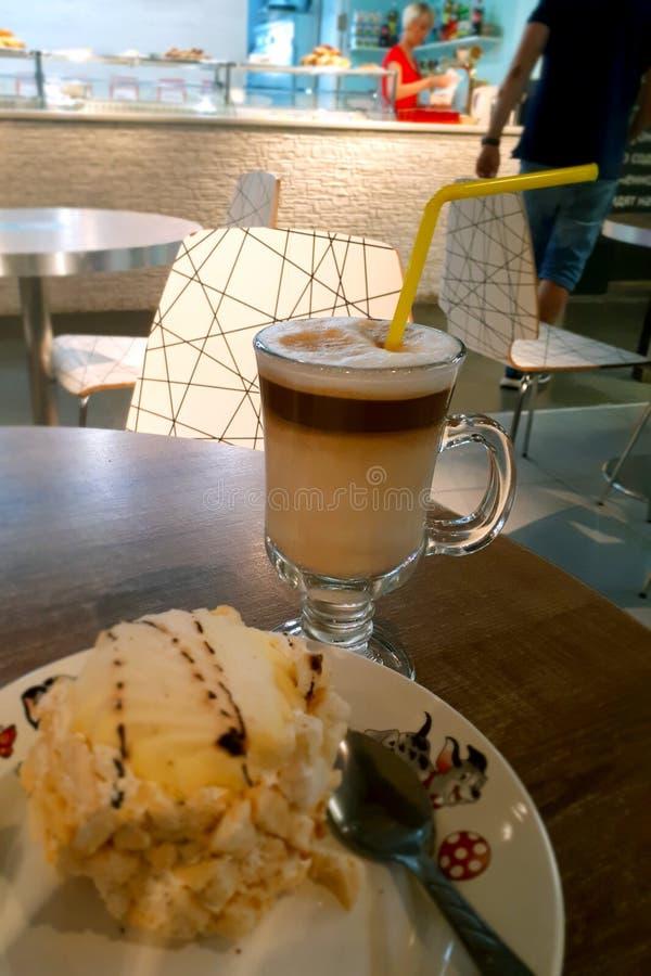 O café do cappuccino está em uma tabela com bolo em uma placa fotografia de stock royalty free