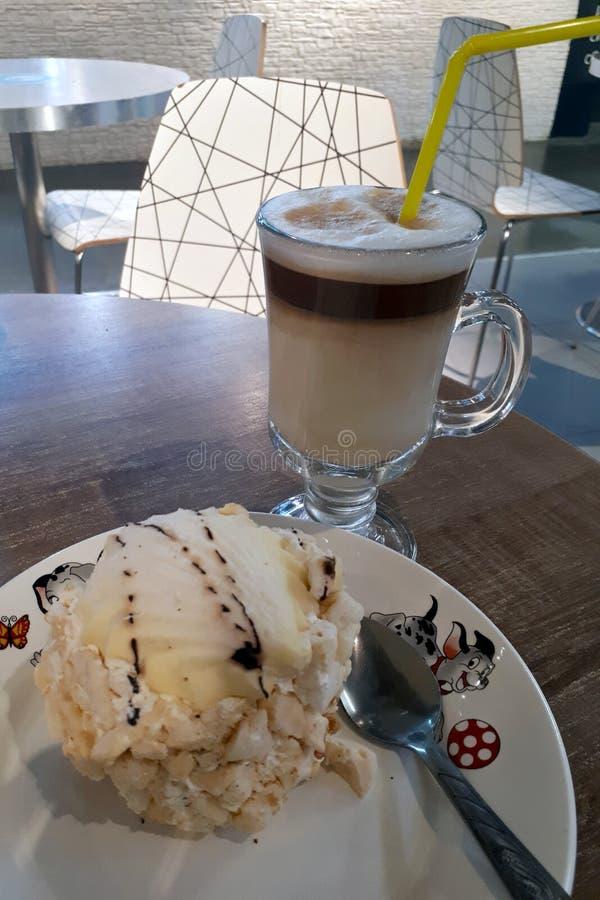 O café do cappuccino está em uma tabela com bolo em uma placa fotografia de stock