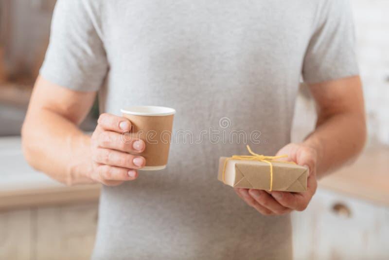 O café do copo do homem da surpresa da manhã envolveu o presente fotografia de stock