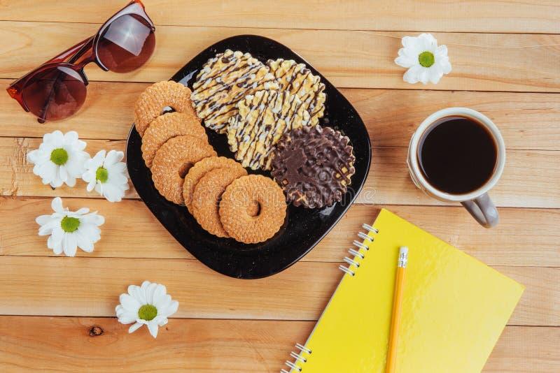 O café do café está em uma tabela de madeira com cookies, almofada e lápis fotos de stock