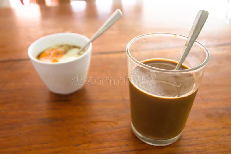 O café e o ovo de fervura tailandeses tradicionais serviram na tabela imagens de stock royalty free