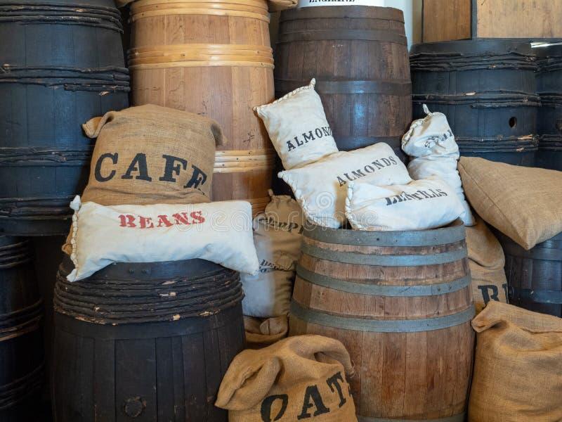 O café, feijões, amêndoas, aveia ensaca o assento em tambores no armazém fotos de stock royalty free