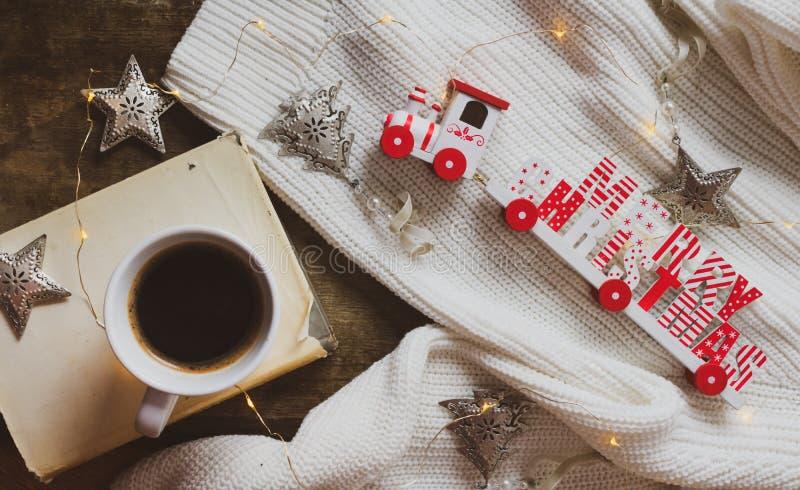 O café, livro, Feliz Natal treina e decorações em um fundo de madeira imagens de stock royalty free
