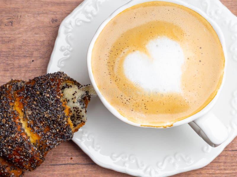 o caf? no cappuccino do restaurante com um cora??o deu forma ? espuma, croissant foto de stock