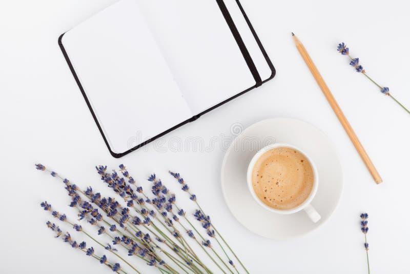 O café, o caderno limpo e a alfazema florescem no fundo branco de cima de Mesa de trabalho da mulher Modelo acolhedor do café da  fotos de stock royalty free