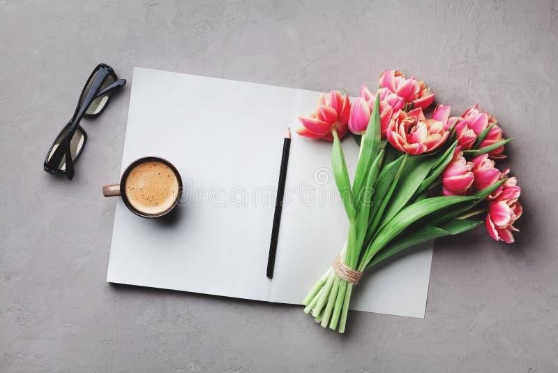 O café, o caderno limpo, os monóculos e a flor bonita na opinião de tampo da mesa de pedra no plano colocam o estilo Mesa de trab imagem de stock royalty free