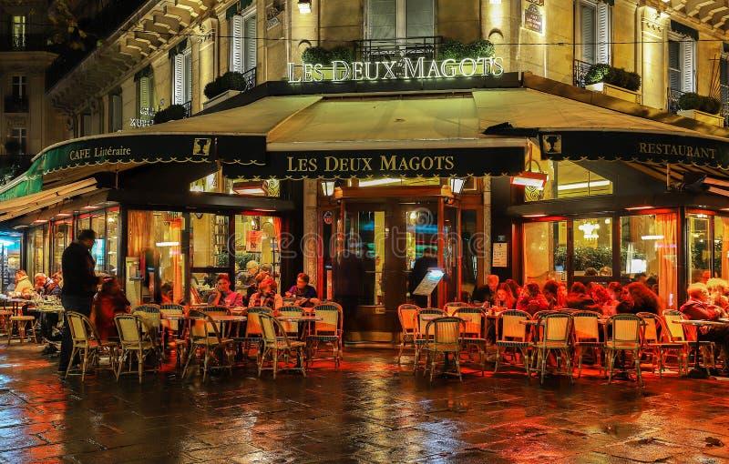 O café parisiense famoso Les Deux Magots na noite chuvosa, Paris, França foto de stock