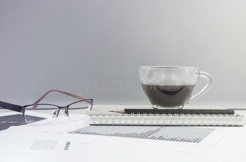 O café preto do close up na xícara de café no livro e no lápis de nota com papel de trabalho na mesa e na parede de vidro de made fotos de stock