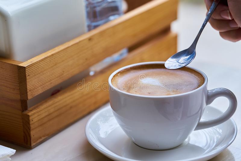 O café quente no copo branco na tabela no café, mão do ` s da mulher toma um café com colher fotografia de stock royalty free