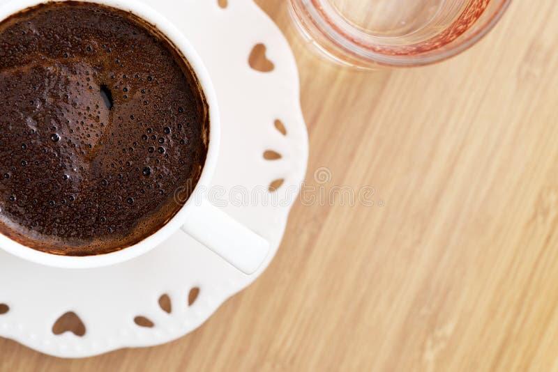 O café turco com água na tabela de madeira e o coração dão forma à vista superior fotografia de stock royalty free