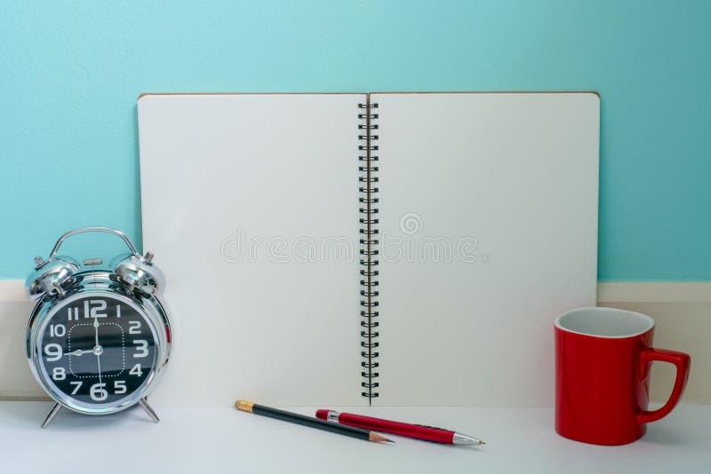 O café vermelho do copo e o metal brilhante cronometram com o caderno da página vazia, c fotografia de stock royalty free
